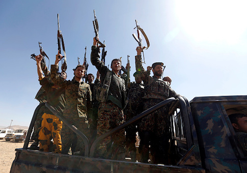 Newly recruited Houthi fighters chant slogans as they ride a military vehicle during a gathering in the capital Sanaa