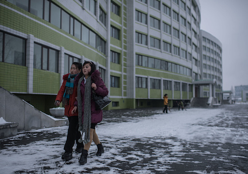 Two women walk outside a dormitory of the Kim Jong-Suk textile mill in Pyongyang