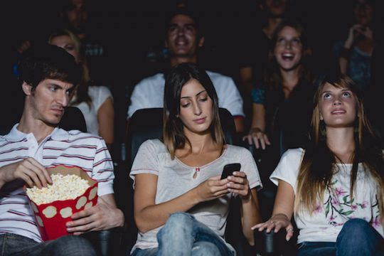 woman using a cell phone in a movie theater