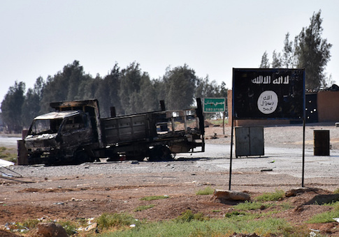 A general view shows a burnt out vehicle next to a banner bearing the Islamic State group's flag
