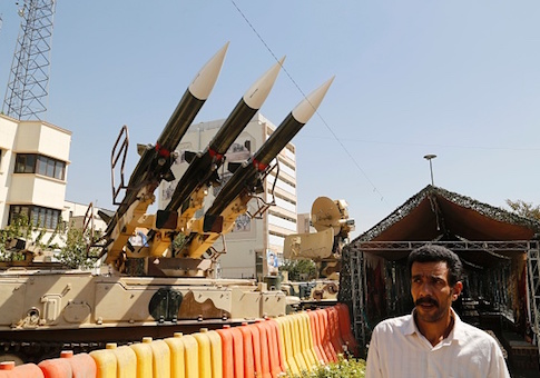 AN Iranian man walks past Sam-6 missiles displayed in the street during a war exhibition
