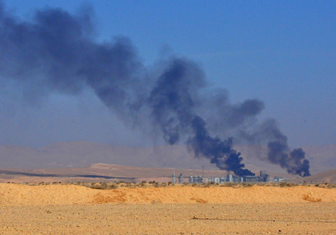 A general view shows smoke billowing from an oil field on the eastern outskirts of Homs
