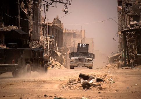 """Iraqi forces patrol a street in west Mosul on July 12, 2017 a few days after the government's announcement of the """"liberation"""" of the embattled city from ISIS"""