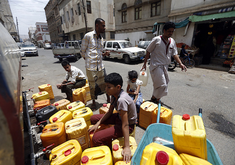 Yemenis arrive to fill jerrycans with safe drinking water from a donated water-tank in the capital Sanaa