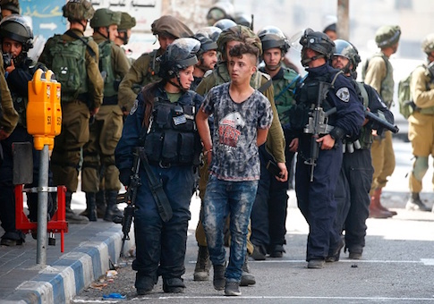 Israeli forces arrest a Palestinian youth during clashes between demonstrators and security forces in the city of Hebron