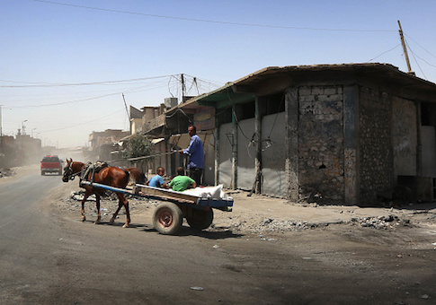 Iraqis ride a cart in western Mosul's old city