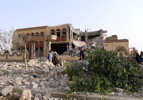 Yemenis walk past a building, housing branches of the Finance Ministry and Central Bank, that was heavily damaged in an airstrike by the Saudi-led coalition