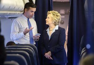 Hillary Clinton looks at a smart phone with national press secretary Brian Fallon / Getty Images