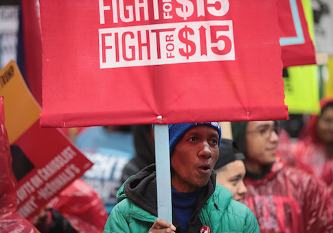Demonstrators fighting for a $15-per-hour minimum wage march through downtown during rush hour on May 23, 2017 in Chicago