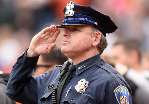 A Baltimore city police officer during the National Anthem at a baseball game / Getty Images