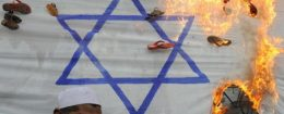 Pakistani activists torch an Israeli flag during a protest