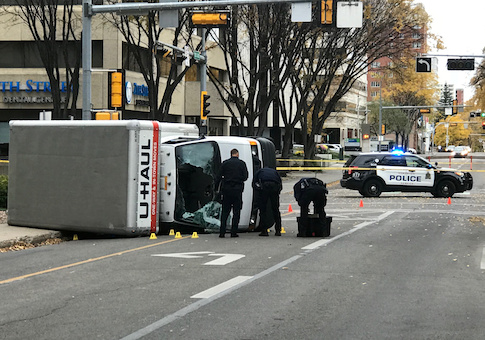 Edmonton Police investigate at the scene where a man hit pedestrians then flipped the U-Haul truck he was driving