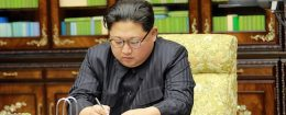 Kim Jong-Un signing an order document of a test-fire of the inter-continental ballistic rocket Hwasong-15