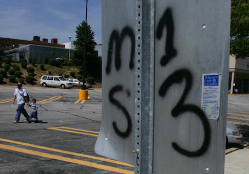 An unidentified man walks with a young boy thru a grocery store parking lot near a traffic sign with the back of it spray painted indicating it as territory for the El Salvaldorian gang MS13 in the Washington, DC, suburb of Silver Spring, Maryland