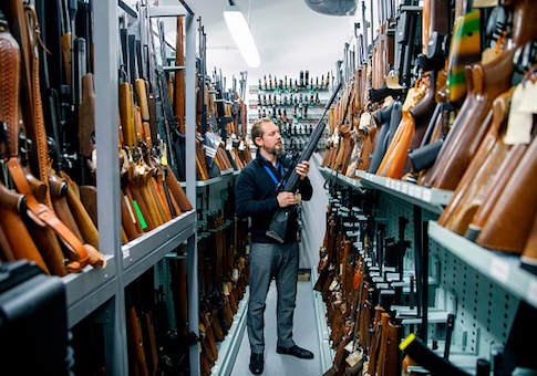 A firearms inspector poses for a photograph with seized and handed in firearms at the storage room of the London Metropolitan Police firearm forensics laboratory