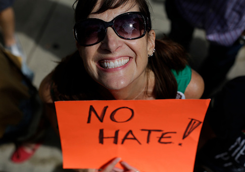 A demonstrator holds a sign during a protest against hate