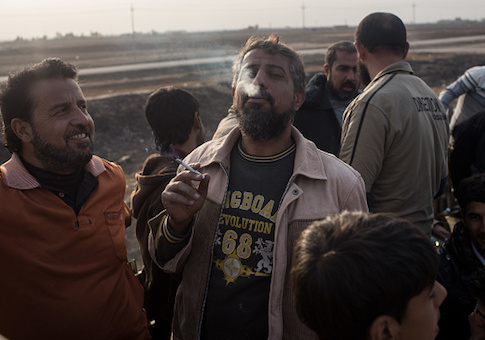 A man smokes his first cigarette after fleeing Mosul