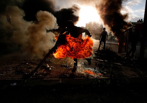 A Palestinian protester runs after catching fire during clashes with Israeli troops at a protest against US President Donald Trump's decision to recognize Jerusalem as the capital of Israel