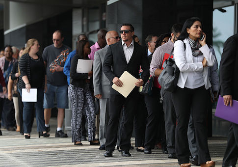 People stand in line as they wait to get into the JobNewsUSA job fair