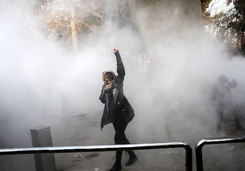 An Iranian woman raises her fist amid the smoke of tear gas at the University of Tehran during a protest driven by anger over economic problems / Getty Images