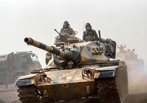 Turkish troops advance near the Syria border at Hassa, Hatay province, on January 22