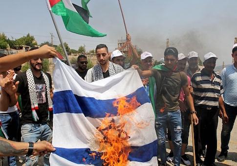 Lebanese and Palestinian youths burn a make-shift Israeli flag