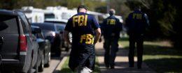 FBI agents walk towards a crime scene on Mission Oaks Boulevard following an explosion in Austin