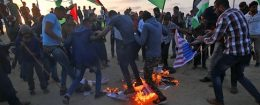 Protesters waving Palestinian flags stamp on burning prints of US flags and President Donald Trump in Gaza