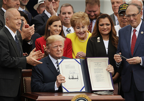 Donald Trump holds up the Veterans Affairs Mission Act he signed