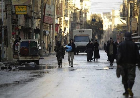 Free Syrian Army fighters walk along a street in Deir al-Zor, eastern Syria, Dec. 12, 2013