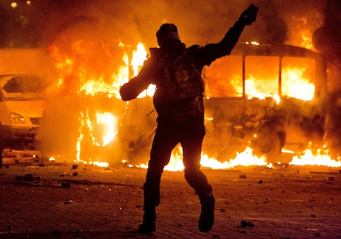 A protester throws a stone towards a burning police bus