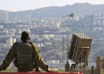 An Israeli soldier is seen next to an Iron Dome rocket interceptor battery / AP