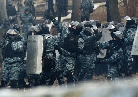 Riot police officers throw stun grenades at anti-government protesters