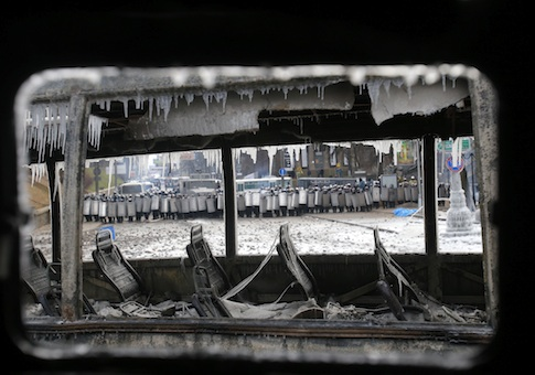 Seen through a vehicle torched by protesters overnight, police officers block a street during unrest