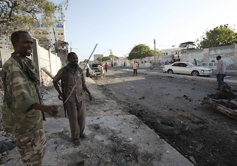 Soldiers assess the aftermath at the scene of an explosion outside Jazira hotel in Mogadishu