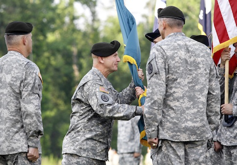 Maj. Gen. H.R. McMaster, center left, hands the Maneuver Center of Excellence flag to Command Sgt. Maj. James Carabello as he assumes command of the MCoE at Fort Benning, Ga.