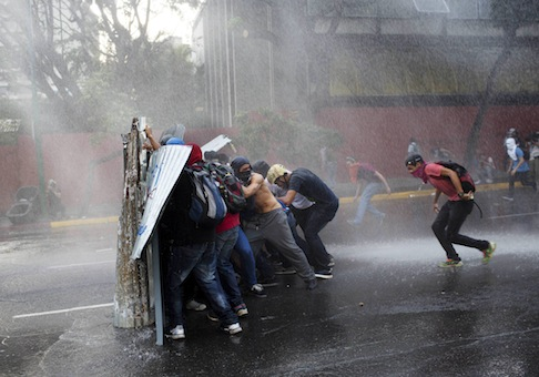 Anti government demonstrators take cover from a police water cannon in Caracas, Venezuela, / AP