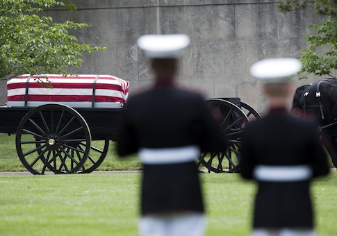 A Marine Corps honor guard watches as a caisson carrying casket