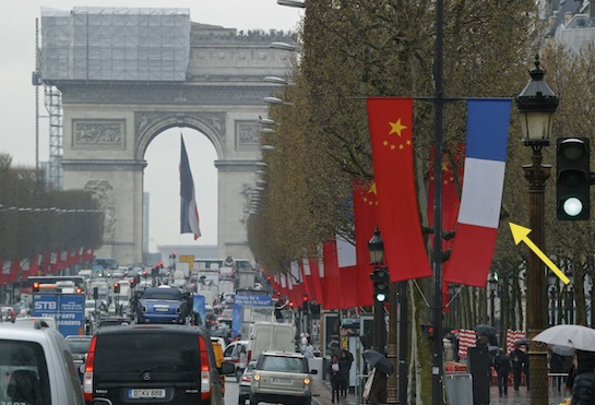 A French flag hangs next to the red flag of communist China in Paris. (AP)