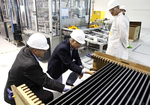 Secretary of the Interior Ken Salazar, second from left, examines solar electric panels as he tours the Abound Solar manufacturing plant