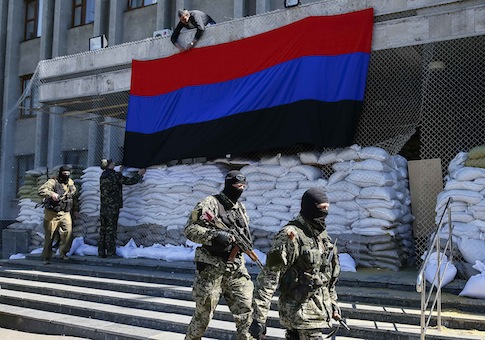 "Pro-Russian armed men walk past activists hanging up a ""Donetsk Republic"" flag outside the mayor's office in Slaviansk"