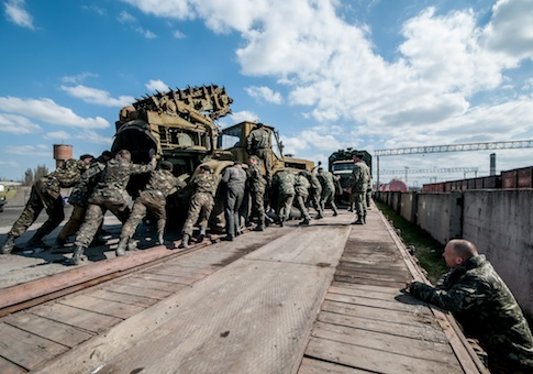 Russian soldiers load Ukrainian military equipment to be shipped to Ukraine