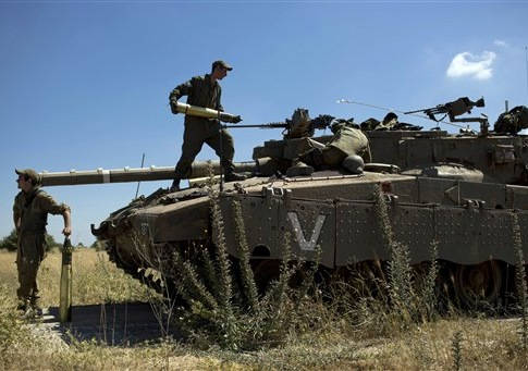 Israeli soldiers load shells in their tank following the first death on the Israeli side of the Golan since the Syrian civil war erupted more than three years ago