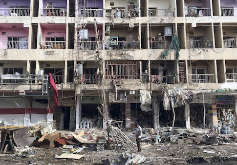 Iraqi civilians inspect the aftermath of a car bombing in the southeastern district of New Baghdad, Iraq, June 8