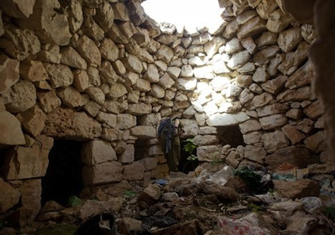 An Israeli soldier inspects a stone structure as they search for three missing Israeli teens