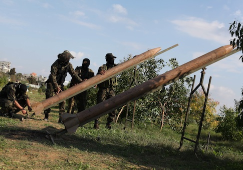 Masked Palestinian militants from Islamic Jihad place homemade rockets during a training exercise on the outskirts of Gaza City