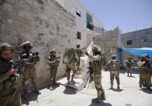 Israeli soldiers patrol during a military operation to search for three missing teenagers outside the West Bank city of Hebron