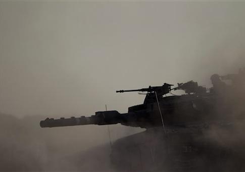 An Israeli tank takes a position along the Israel-Gaza Border