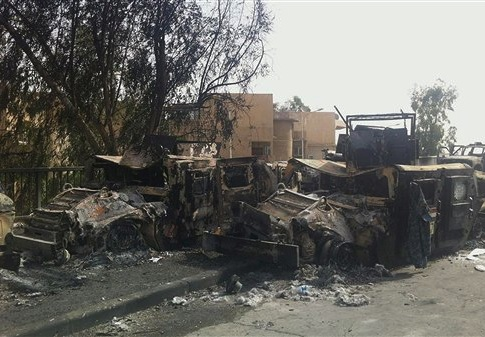 Iraqi army armored vehicles are seen burned on a street of the northern city of Mosul