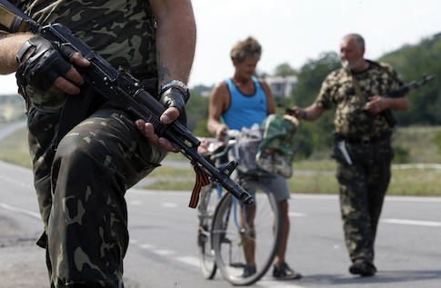 Armed pro-Russian separatists stand guard at a checkpoint in the settlement of Yasynuvata outside Donetsk